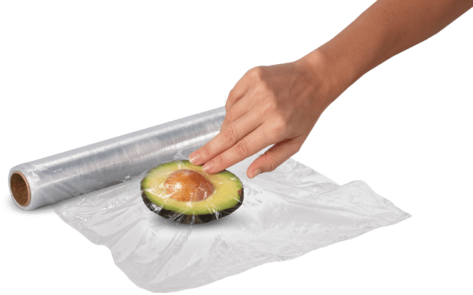 Avocado being placed in a paper bag with a Banana